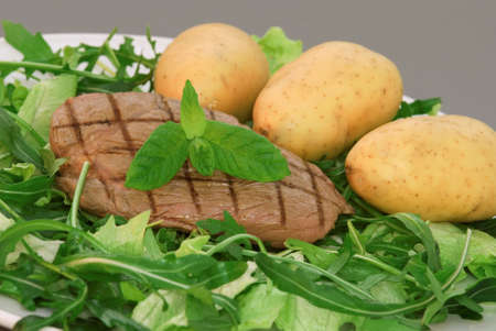 Juicy steak served on a bed of salad with  potatoes photo