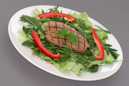 Griddled steak on green leaf salad with red peppers garnish photo