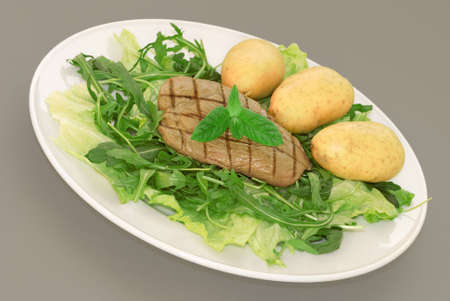 A plate of green leaf salad with  potatoes and steak photo