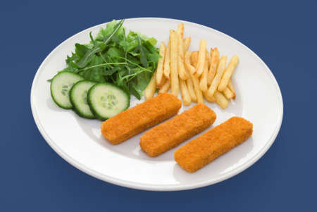 Three fish fingers on white plate with fries and salad - shot on a blue background