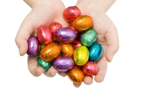 A child holding out a handful of colourful Easter Eggs photo