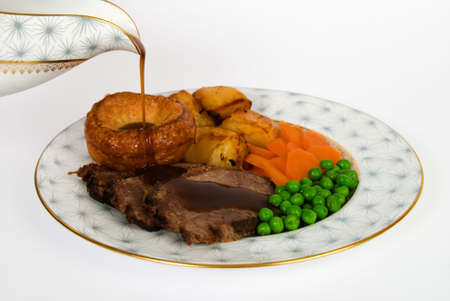 gravy: Roast beef with yorkshire puddings, gravy being poured