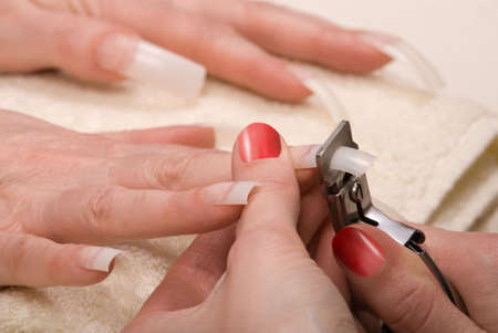 Manicurist trimming nail extensions on clients fingers photo