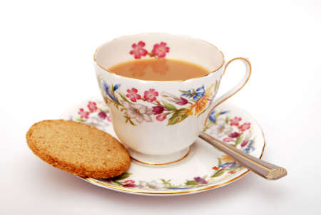Cup of Traditional English tea with biscuit on white background photo
