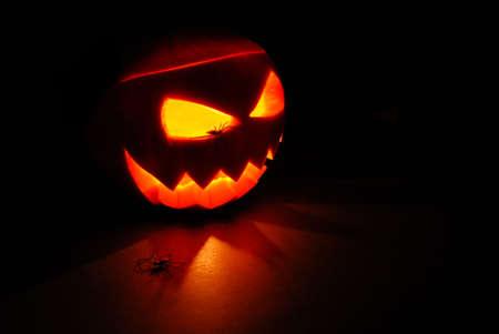 menacing: Halloween Jack O Lantern or Pumpkin internally lit casting shadows with two spiders Stock Photo