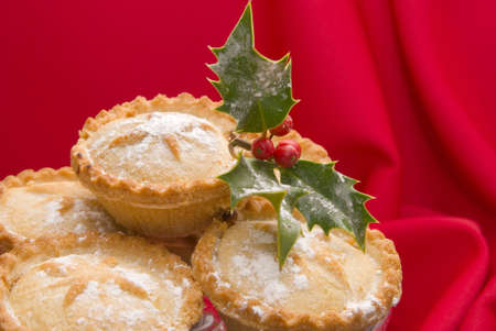 minced pie: Christmas mince pies with holly and berries dusted with icing sugar on red tablecloth Stock Photo
