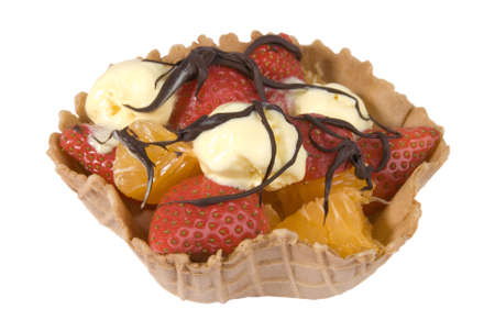 Waffle fruit basket filled with strawberries, satsumas and ice cream drizzled with chocolate sauce photo