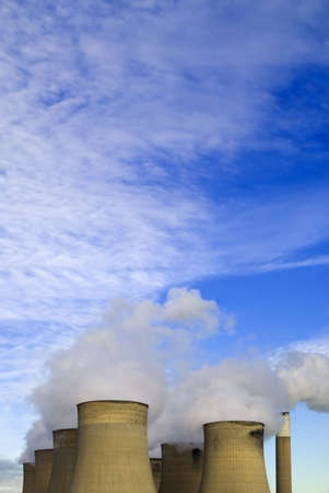 powerstation: Cooling towers with warm lighting under blue sky with clouds Stock Photo