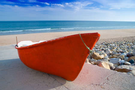 on ramp: Small old red fishing boat on the beach Stock Photo
