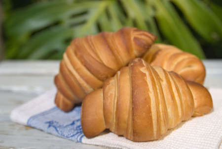 Three large handmade croissants in a rustic setting Stock Photo - 3042515