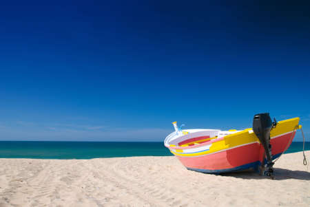 beached: Bright painted small fishing boat in the beach