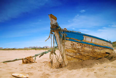 holed: Dilapidated fishing boat in the sand Stock Photo