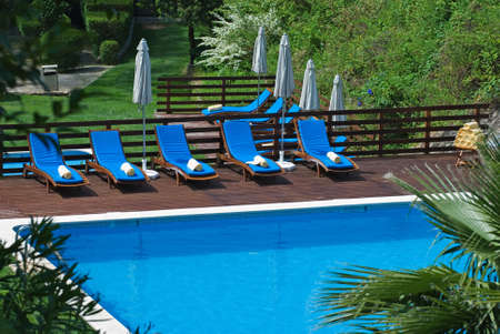 loungers: A row of recliners around a luxury resort swimming pool Stock Photo