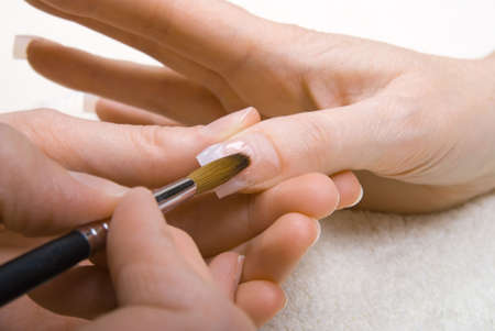 Professional manicurist applying liquid acrylic to nail extensions