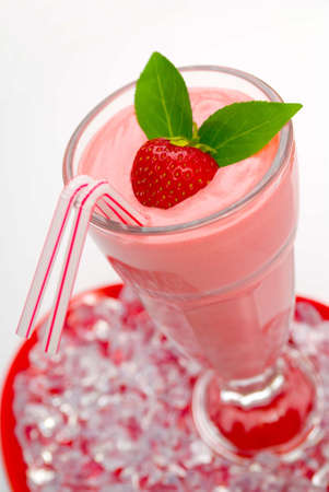 Strawberry fruit drink with ice, mint sprig and straws photo
