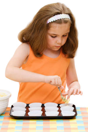 Young girl putting out the cake mixture into paper cases, isolated on white background Stock Photo - 3333436