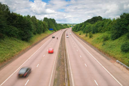 carriageway: Motorway cutting through the rural countryside - motion blue to vehicles