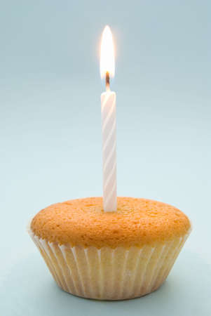 Plain cupcake with single white candle emphasising simplicity photo