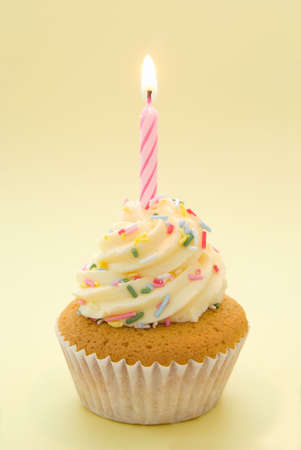 Cupcake with icing and single candle with yellow theme Stock Photo - 3430682