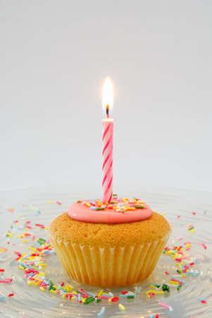 velas de cumplea�os: Cupcake con velas en placa de vidrio con dulces sprinkles