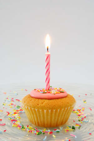 Cupcake with candle on glass plate with candy sprinkles photo