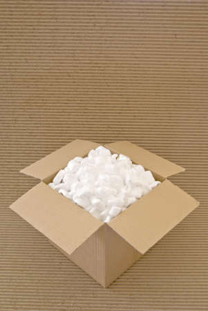 despatch: Cardboard carton filled with packing chips on a corrugated board background Stock Photo