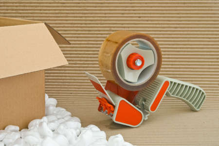 packing boxes: Tape gun and packaging materials Stock Photo