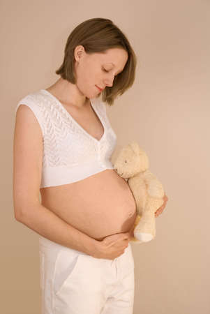 contemplates: Pregnant woman holds a teddy bear whilst caressing her tummy