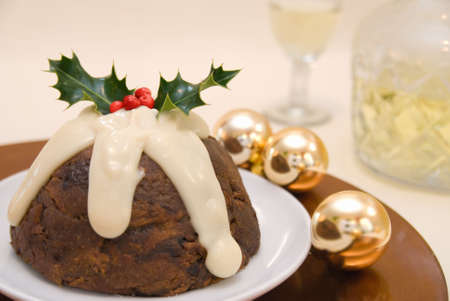 christmas pudding: Christmas pudding with brandy sauce decorated with holly