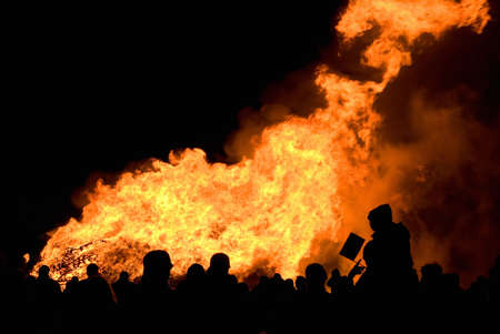 campfires: Crowd in silhouette enjoying a large bonfire Stock Photo