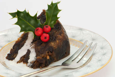 plum: Slice of Christmas pudding with fork & decorated with holly Stock Photo