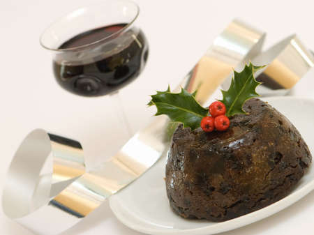 Christmas pudding decorated with holly with a glass of wine photo