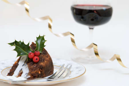 Christmas pudding slice with brandy sauce and glass of wine photo