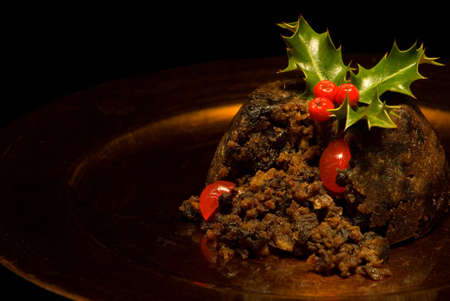 christmas pudding: Cut Christmas pudding with holly & berries Stock Photo