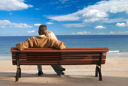 to cuddle: Couple looking out to sea Stock Photo
