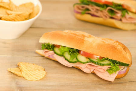 Cut ham salad baguette with crisps on a rustic table photo
