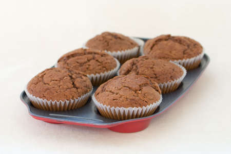 Freshly baked muffins still warm in the tray photo