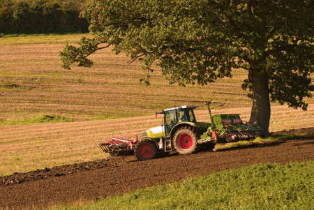 Tractor ploughing the field in autumn photo