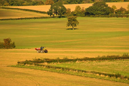 Autumn patchwork farmland with tractor photo