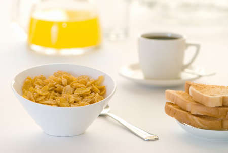 cereal bowl: Breakfast table with cereal, toast, coffee and orange juice