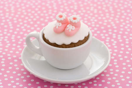 baptism background: Christening cupcake with pink booties for a girl on spotty ground