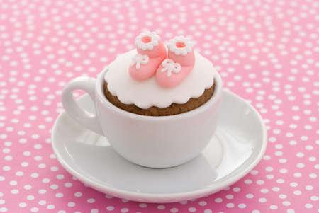 bautismo: Cupcake bautizo con botines de color rosa para una ni�a en terreno irregular Foto de archivo