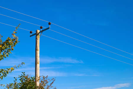 electricity pole: Power lines on wooden pole through rural land Stock Photo