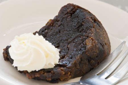 christmas pudding: A slice of Christmas pudding with cream Stock Photo