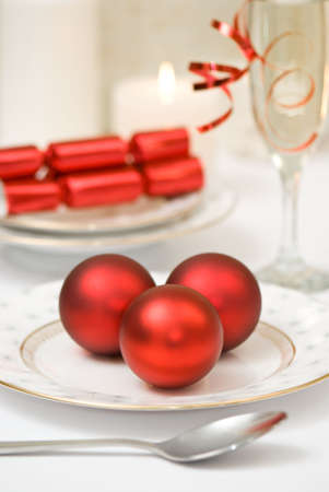 Christmas table setting with champagne and red baubles and crackers photo