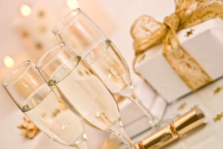 Champagne and gifts with lit candles in background photo