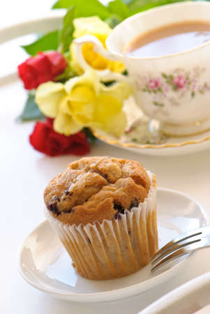 Baked muffin with English style tea and flowers on tray - high key photo