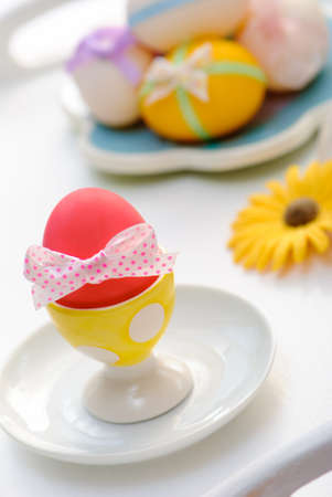 Decorated Easter eggs in eggcup with spotty bow photo