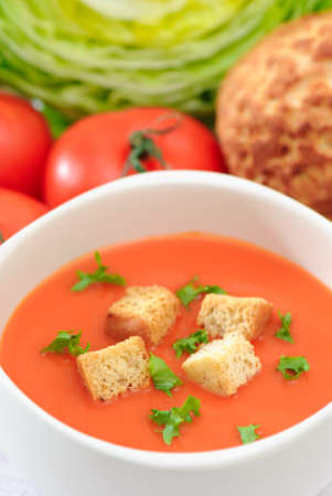 Bowl of tomato soup with croutons and garnish
