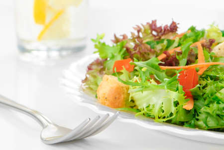 water cress: Fresh green salad with glass of mineral water in background